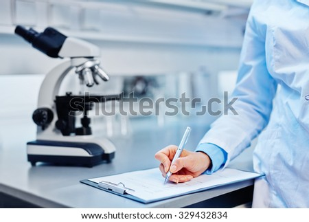 Young chemist making notes in lab
