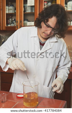 young chemist work with yellow reagent in lab - stock photo