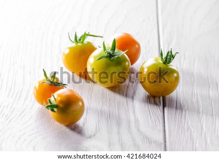 young cherry tomato on white wooden background - stock photo