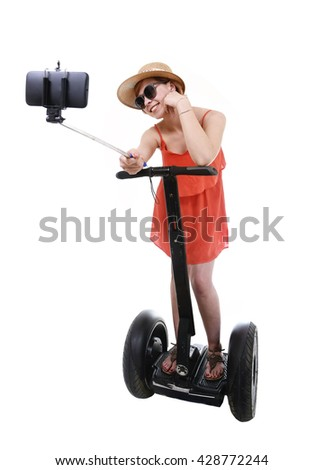 young chic tourist woman taking selfie photo with mobile phone while riding on segway urban transport having fun isolated on white background in vacation tourism concept - stock photo