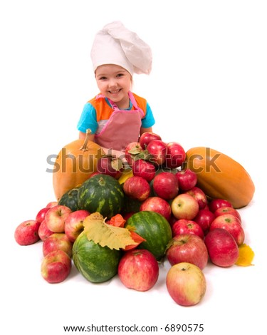 Young chief cook - happy smiling girl with lots of fruits