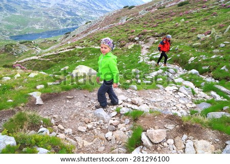 Young child ascending on rough trail with his mother following - stock photo