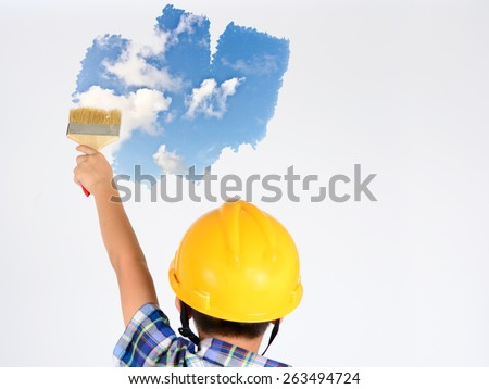 young child boy painting blue sky over white wall - stock photo