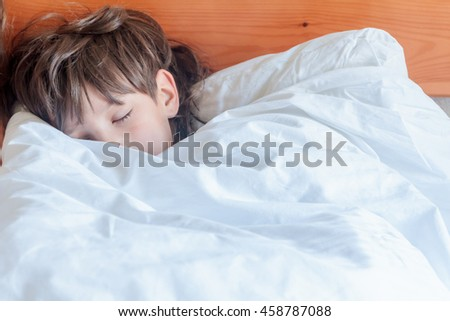young child boy sleeping in bed at home, indoor portrait - stock photo