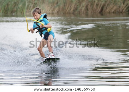 young child boy wake boarding - stock photo