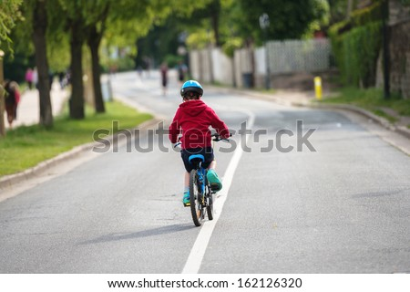 young child doing the bike alone in the middle of the road - stock photo