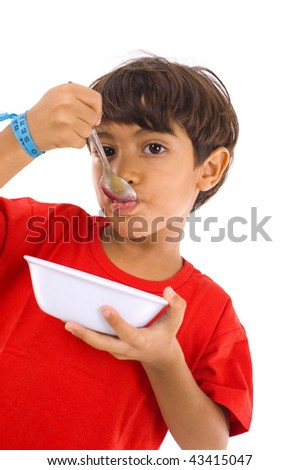 Young Child eating using a plate and spoon . - stock photo