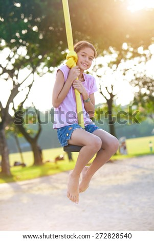 Young child enjoying on balancing activity at the outdoor park in evening sun. - stock photo