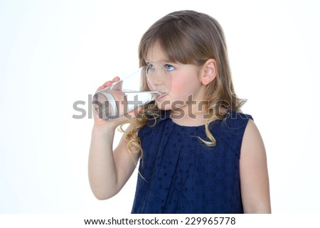 young child enjoys a glass of fresh water - stock photo