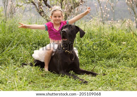 Young child girl dressing up in a fancy dress, sitting on her great dane dogs back holding her arms up like a heroine. Proud dog owner playing with her pet and enjoying a summer holiday together. - stock photo