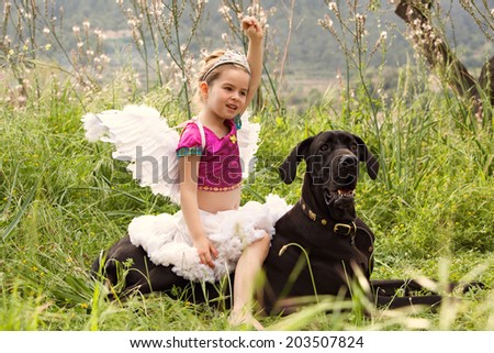 Young child girl dressing up in a fancy dress with wings, sitting on her great dane dogs back holding her fist up like a heroine. Proud owner playing with her pet enjoying a summer holiday together.