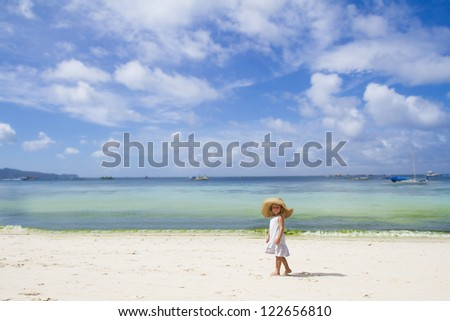 young child girl in summer hat on tropical sea background