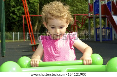 Young child having fun on a ride at the playground. The ride is green and is a see-saw and the pretty toddler is wearing a pink top. She has blonde curly hair and is holding on tight. - stock photo