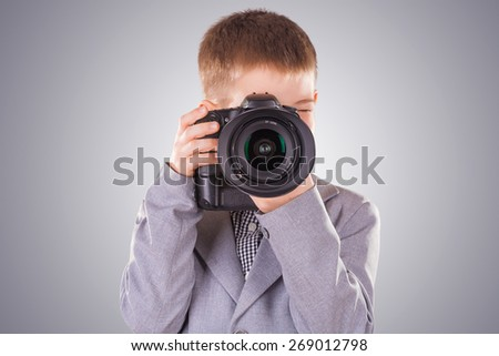 young child holding a dslr camera on a white background - stock photo