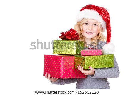 Young child holding large stack of Christmas presents wearing a Santa hat isolated on white - stock photo