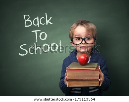 Young child holding stack of books and back to school written on chalk blackboard - stock photo