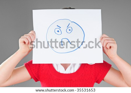 Young child holding up sign to mask true emotion - psychology concept - stock photo