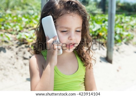 Young child in a yellow shirt speaking at phone outside in a park with green plants in the background - stock photo