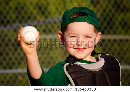 Young child in catcher's gear throwing baseball - stock photo