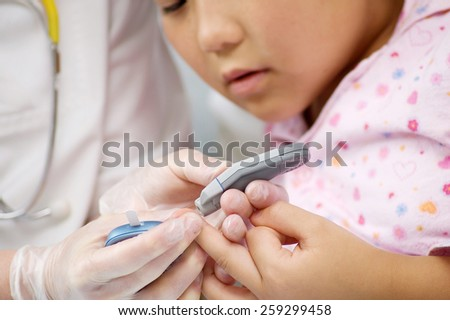 Young child in hospital getting a blood test with doctor - stock photo