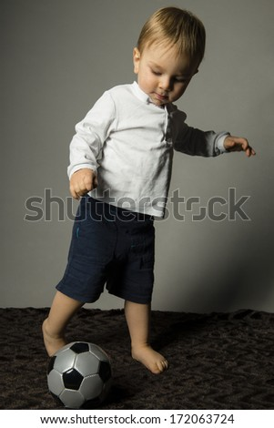 young child is playing with a ball - stock photo