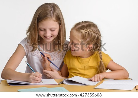 Young child is smearing sister's hair with brush and laughs. Beautiful girl is busy with her drawing. Stationery on the wooden desk. - stock photo