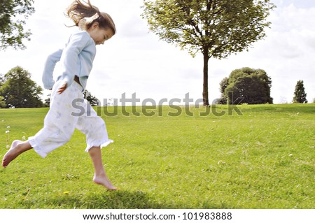 Young child jumping on a park's green grass. - stock photo