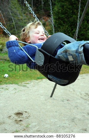 Young child laughing while enjoying ride in safe swing at park - stock photo