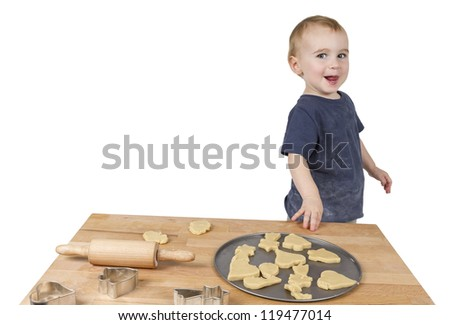 young child making cookies on small wooden desk - stock photo