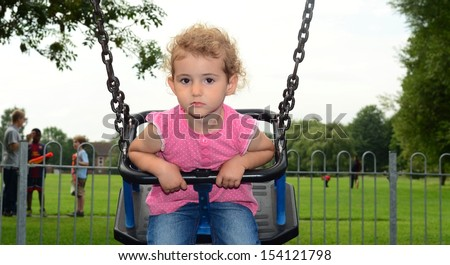 Young child on a swing at the park. Toddler girl at the playground. She is wearing pink top, blue jeans and has blonde curly hair. Grass, trees and a white cloudy sky are the backdrop. - stock photo