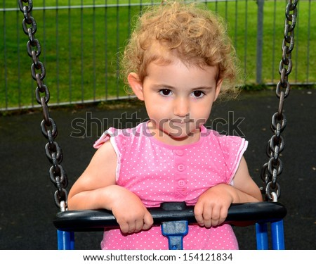 Young child on a swing at the park. Toddler girl smiling on a swing at the playground. She is wearing pink top, blue jeans and has blonde curly hair. Green grass backdrop. - stock photo