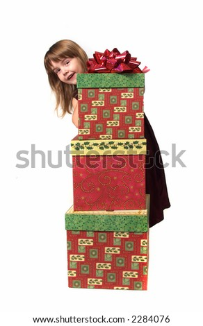 Young Child Peeking From Behind Christmas Gifts - stock photo