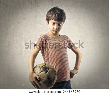 Young child playing football  - stock photo