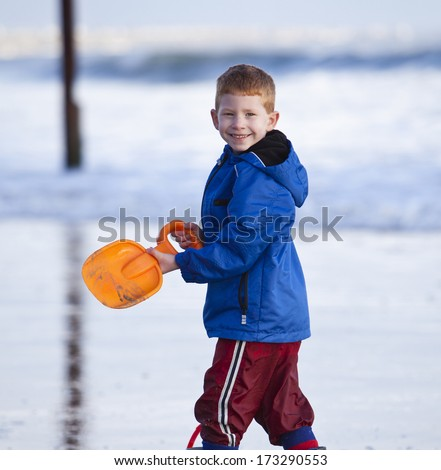 Young child playing on a beach in winter