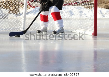 Young child playing outdoor pond ice hockey - stock photo