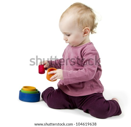 young child playing with colorful toy blocks in white background