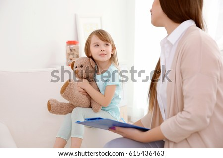 Young child psychologist working with little girl