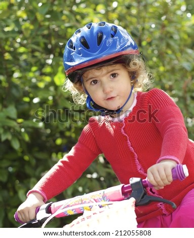Young child riding her bike. - stock photo