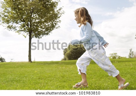Young child running on a park's green grass. - stock photo