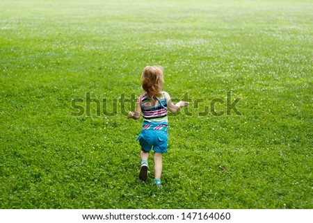 Young child running through a meadow - stock photo