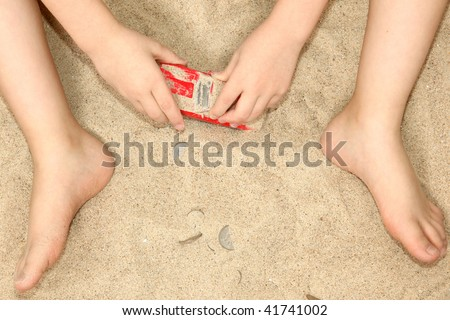 Young child's hands and feet in sand playing with car and money. - stock photo