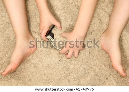 Young child's hands and feet in sand playing with wallet.