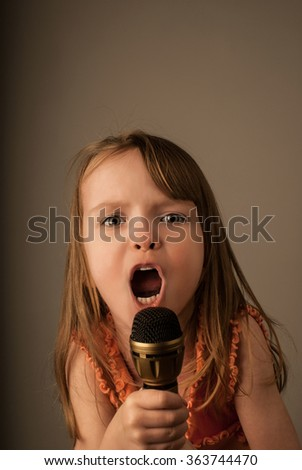 Young child singing into a handheld microphone with expressive open mouth, on plain neutral background - stock photo