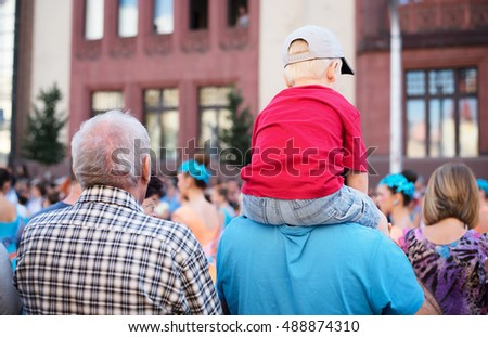 Young child sitting on his father shoulders in the street