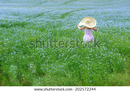 Young child standing in a flower field, wearing a large sun hat - stock photo