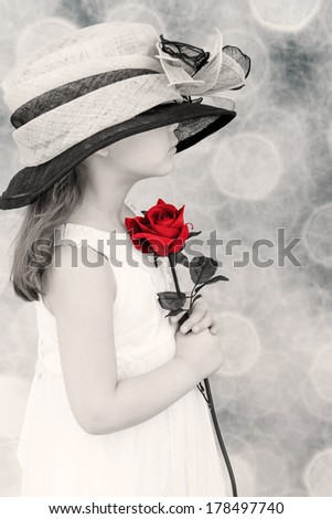 Young child wearing an over sized hat, holding a red rose with a Black and white background. - stock photo