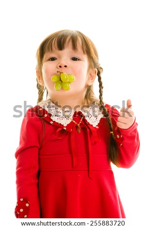 Young child with green grapes in the mouth - stock photo