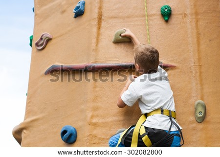 young children climbing on outdoor climbing wall