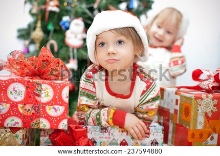 Young children find gifts under the tree on Christmas - stock photo
