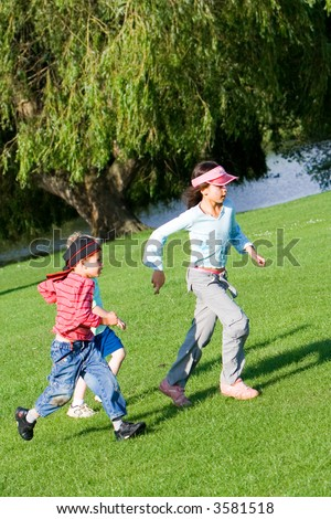 Young children having fun playing chase in the park on a lovely summer's afternoon. - stock photo